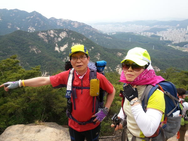 Hiking club leader Kang Seok-bong and hiker Lee Geun-rye atop Bukhansan Mountain, which overlooks Seoul. Kang says health permitting, he'll continue hiking into his 70s.
