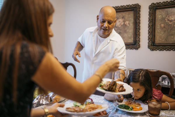 Jennifer Carione puts food on Dan Carione's plate while their daughter Sophia eats dinner at their home in Brooklyn, N.Y.