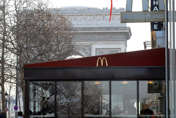 "The Arc de Triomphe is visible behind a McDonald's restaurant on the Champs Elysees in Paris, France. The nation is now McDonald's second-biggest market, but one historic neighborhood known as ""the belly of Paris"" has pledged to keep it out."