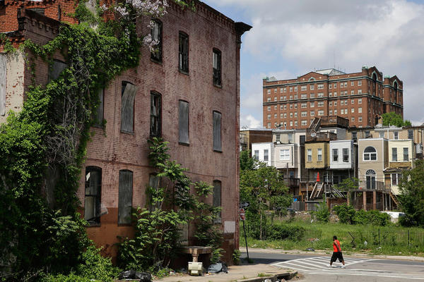 A man walks past a blighted building in the Penn-North neighborhood of Baltimore.