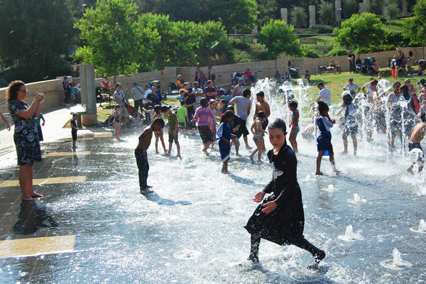 To keep cool on a hot day, Tzipora Baranas joins scores of other children in a Jerusalem fountain. She is fully clothed, in accordance with her family's religious beliefs.