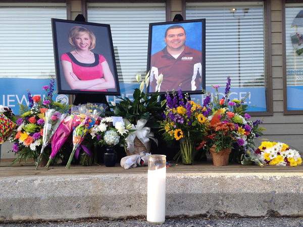 A candle burns in front of a memorial for two slain journalists, Alison Parker and Adam Ward.
