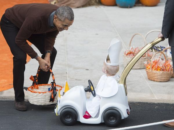 """President Barack Obama greets a young child dressed as the Pope and riding in a """"Popemobile"""" as he hands out treats to children trick-or-treating for Halloween on the South Lawn of the White House in Washington, DC."""