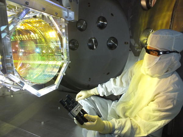 A LIGO optics technician inspects one of LIGO's core optics by illuminating its surface with light. It is critical to LIGO's operation that there is no contamination on any of its optical surfaces.
