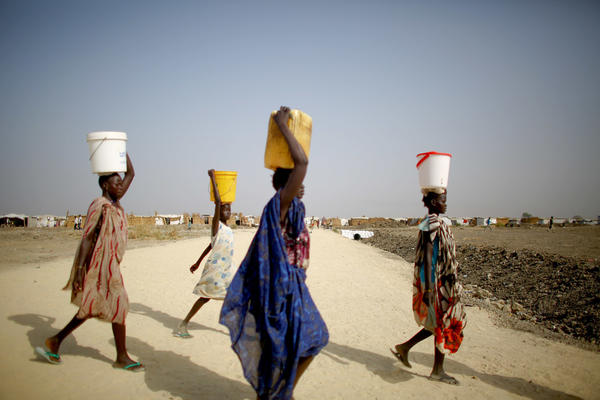 It's a daily ritual: Women carry water from communal taps back to their shelters.