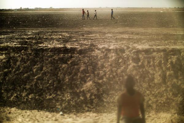 Residents walk across a dusty plain inside the U.N. Protection of Civilians camp near Bentiu, South Sudan.