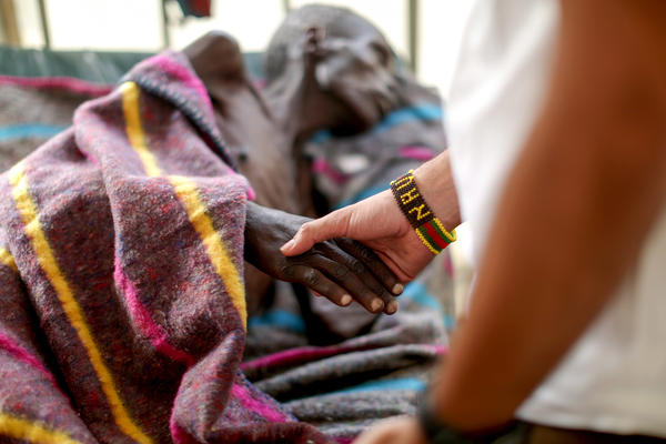 The kids in the camp made a beaded bracelet for Dr. Nav, who clasps the hand of a patient in the tuberculosis ward.