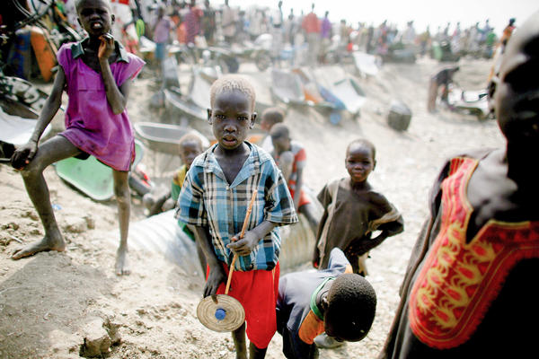 A boy holds a makeshift toy. Behind him, young men wait with wheelbarrows for food rations to be distributed.