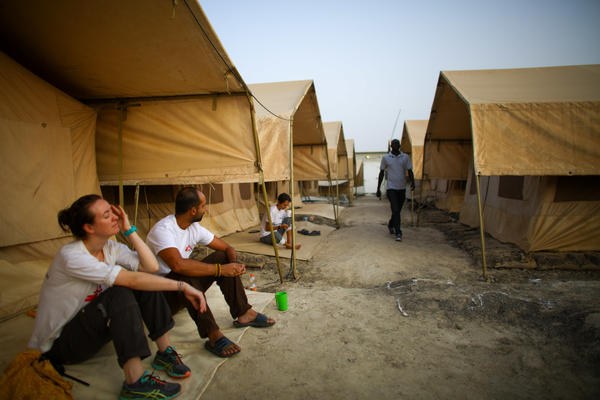 Morning at the MSF hospital compound in Bentiu, South Sudan. The two doctors, Jiske Steensma (left) and Navpreet Sahsi, sit in front of the tents that serve as living quarters for the international workers during their three-to-six-month stints.