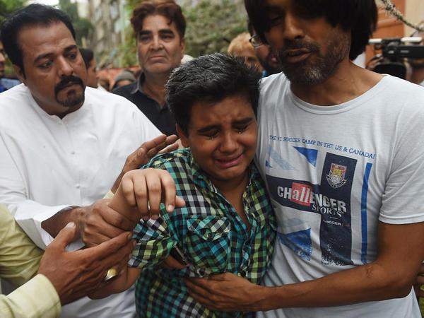 Relatives comfort Mujjudid Sabri (front, center), son of Pakistani singer Amjad Sabri, who was killed Wednesday in an attack by gunmen in Karachi.
