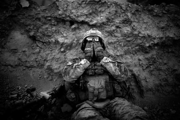 """Marine Lance Cpl. Anthony Espinoza wipes the sweat out of his eyes at the end of a daylong patrol out of the Sangin District in southern Afghanistan in May 2011. <a href=""""http://www.npr.org/sections/pictureshow/2011/05/13/136213445/in-afghanistan-flowers-call-the-shots"""">Read the story.</a>"""