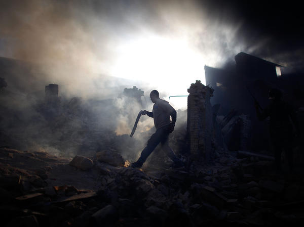 """A man carrying a shotgun walks through a collapsed burning building while trying to keep looters at bay on the streets outside Port-au-Prince, in January 2010. <a href=""""http://www.npr.org/series/480930677/david-gilkeys-work/archive?date=1-31-2010"""">Read the stories from Haiti.</a>"""