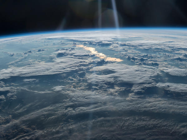Earth as seen by the Expedition 47 crew on May 31, 2016, from the International Space Station — looking from northwestern China on the bottom into eastern Kazakhstan. The large lake in Kazakhstan with golden sun glint is the crescent-shaped Lake Balkhash, the second largest lake in Central Asia.