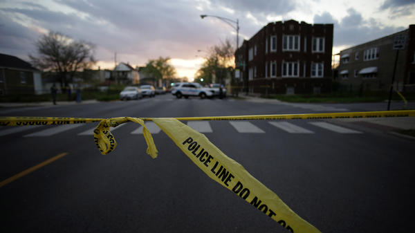 Police tape blocks off a street where a 16-year-old was shot and killed and another 18-year-old was shot and wounded on the on April 25 in Chicago.