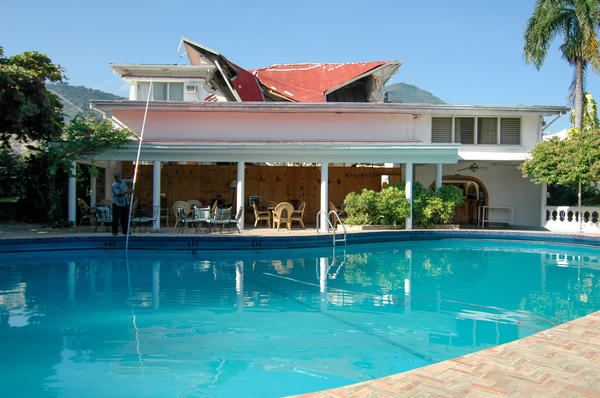 The hotel continued to operate after the devastating 2010 earthquake. The collapsed roof is visible behind the pool.