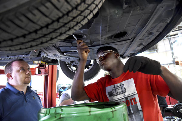 Teacher Daniel Gibbs (left) watches as Devonte Kirkland changes the oil in a car at Gardendale High School in Gardendale, Ala. Kirkland takes a bus each morning to Gardendale for an auto technology class since it is not offered at Center Point High School where he is a student.