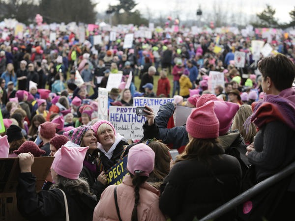 """Led by women in pink """"pussy hats,"""" hundreds of thousands of people packed the streets of Washington and other cities in a massive outpouring of opposition to America's new president, Donald Trump."""
