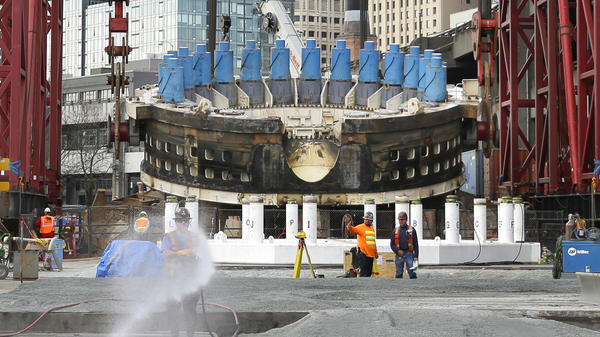 "Workers prepare a gravel pad as a massive crane is used to lift a 2,000-ton section of the tunnel boring machine known as ""Bertha"" in March 2015. The project was stalled for two years as engineers struggled to repair the gigantic machine."