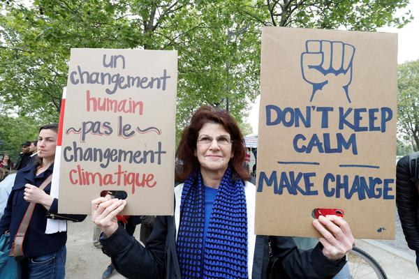 "People take part in the March for Science in Paris. The sign reads: ""A human change, not a climate change"""