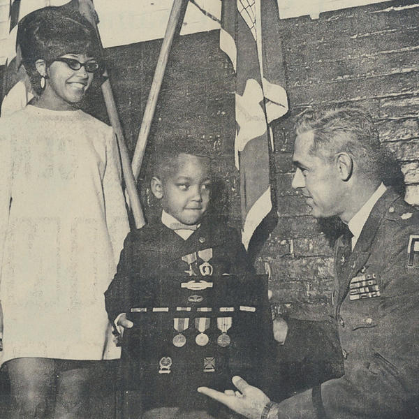 A picture from a local Connecticut newspaper of Robert Howard II accepting his father's medals that were awarded posthumously the year of his death, while his mother Roberta Vincent looks on.