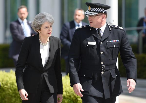 Britain's Prime Minister Theresa May walks with Chief Constable of Greater Manchester Police Ian Hopkins as she arrives at the force's headquarters in Manchester on Tuesday following a deadly terrorist attack the night before.