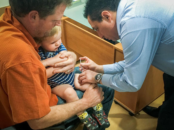 Erik Vance holds his son while a pediatrician administers vaccinations.