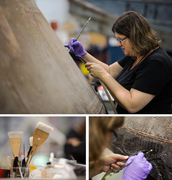 Objects conservator Lisa Young, of the National Air and Space Museum, cleans the honeycomb lattice by using a small bristled paint brush to flick dust from the capsule into the vacuum cleaner.