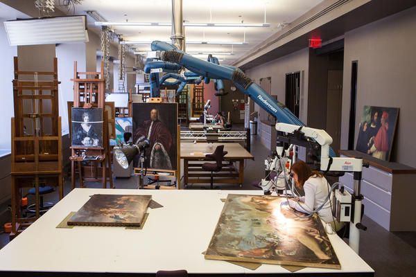Joanna Dunn works to restore Jacopo Tintoretto's <em>Summer</em>, c. 1555. The blue vacuums suspended from the ceiling assist with ventilation.