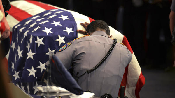 A Baton Rouge police officer kneels at the casket of Cpl. Montrell Jackson, one of three officers ambushed and killed by a gunman July 17, 2016.