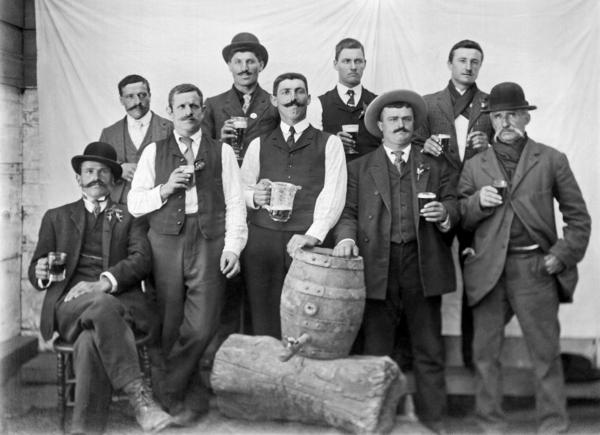 A group of men with full glasses proudly pose with their keg of beer in San Francisco, 1895.