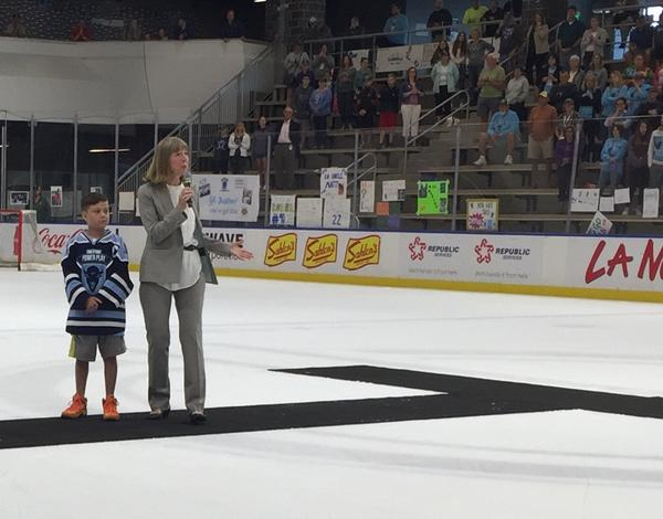 Dr. Candace Johnson of Roswell Park Cancer Institute speaks following the conclusion of the 11 Day Power Play. Joining her was Emmett Jakubowski, a cancer patient and the game's official mascot.