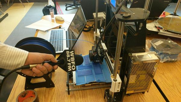 """A tabletop 3-D printer fabricates name tags for the students and teachers of the """"Hand in Hand"""" program."""