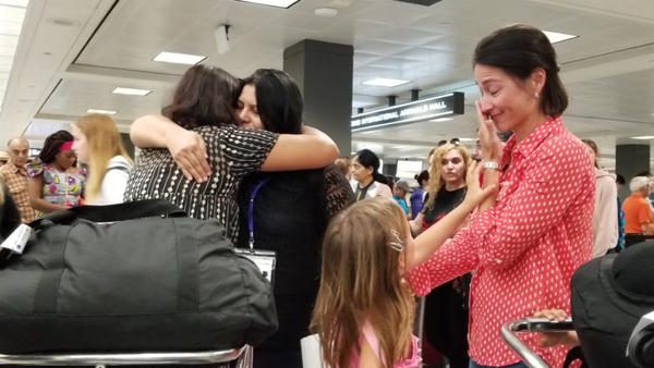 Sisters Rahila, left, and Shaista Sadiq, right, embrace at Dulles Airport as family friend Kristin Kimbart looks on. The sisters went through a two year vetting process before being admitted as refugees to the U.S. Now, they're among the last refugees to be resettled in the area before new refugee admissions guidelines go into effect next week. (Carmel Delshad/WAMU)