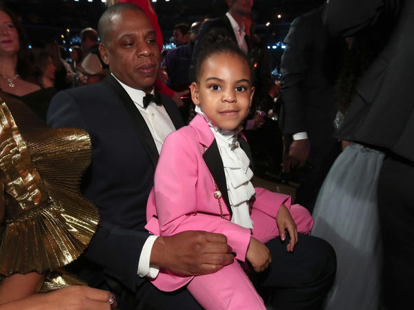 Blue Ivy Carter sits on her father, Jay-Z's lap at The 59th Grammy Awards.