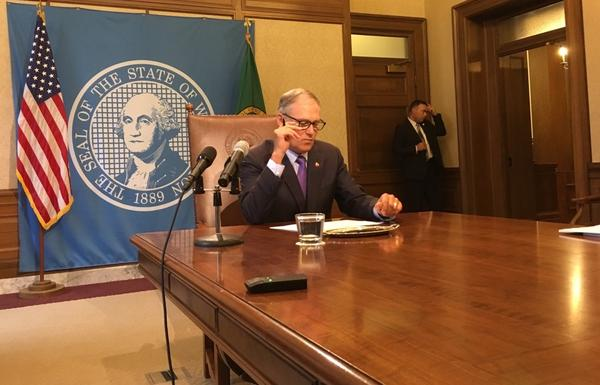 Washington Gov. Jay Inslee prepares to act on a business and occupation tax at the Washington capitol.