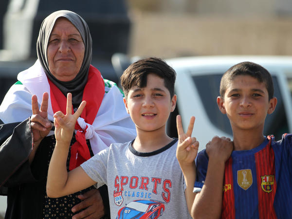"Iraqi civilians in Mosul's Old City flash the ""victory"" sign as they celebrate the government's announcement of the ""liberation"" of the embattled city Sunday."