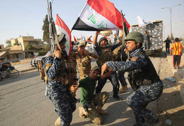 "Iraqi federal police members celebrate in the Old City of Mosul on Sunday, after Iraqi Prime Minister Haider al-Abadi's office said he was in ""liberated"" Mosul to congratulate ""the heroic fighters and the Iraqi people on the achievement of the major victory."""