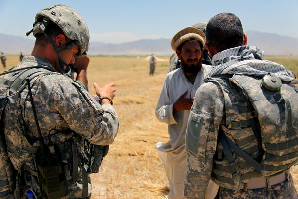 An Afghan interpreter (right) helps a U.S. soldier gather information from a local resident in this 2010 photo.