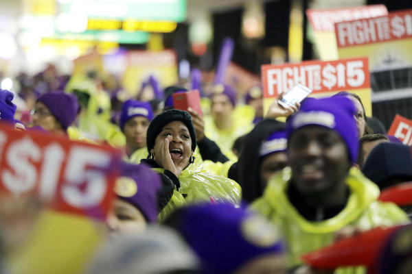 A woman shouts while marching with service workers asking for $15 minimum wage pay during a rally at Newark Liberty International Airport, Tuesday, Nov. 29, 2016, in Newark, N.J. The event was part of the National Day of Action to Fight for $15. (Julio Cortez/AP)