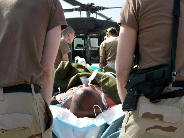 Medics and nurses load an injured American soldier onto a helicopter during the Iraq war. The Military Accessions Vital to the National Interest program is aimed at immigrants with special skills, such as in medicine.