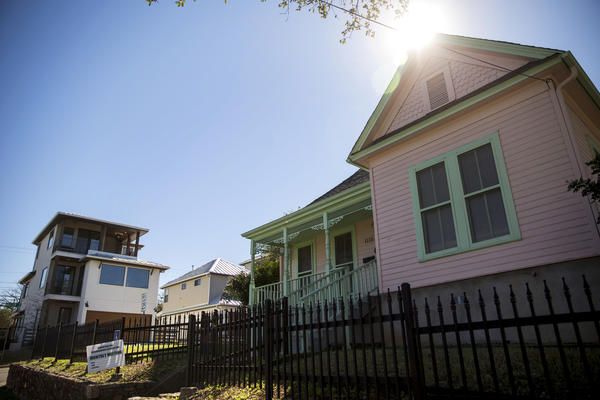 A new multi-story residential building (left) and an older style one-story space sit side by side on 12th Street in the East Austin neighborhood of Austin, Texas. The neighborhood has experienced a strong wave of gentrification, which often pushes people out of the now trendy area.
