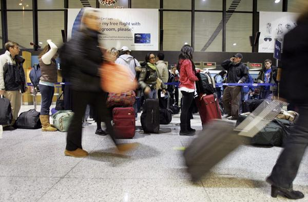 Travelers walk through as others wait in line at Terminal C in Logan International Airport in 2007. (Elise Amendola/AP)