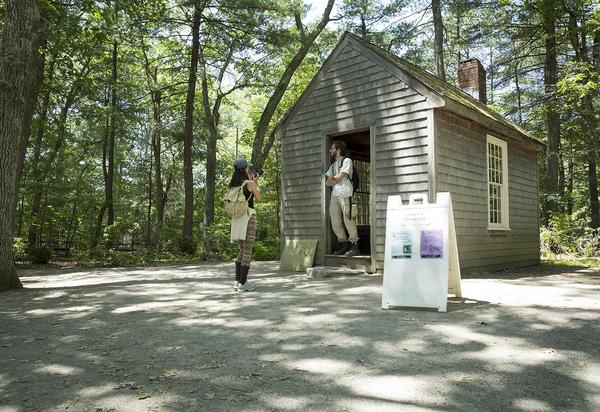 Visitors Christopher Watt, of Wilmington, and Eleanor Vanderzwan of New Zealand, take photos at the recreation of Thoreau's Walden Pond. cabin. (Robin Lubbock/WBUR)