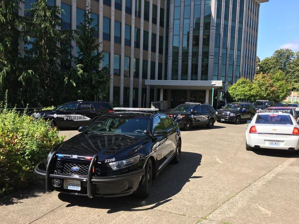 Patrol cars block the entrance of the Washington Department of Licensing building as officers investigate reports of a possible gunshot July 12, 2017.