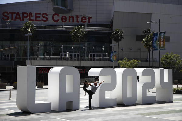 Yoga instructor Michael Phillip poses with a Los Angeles 2024 sign outside Staples Center, Friday, May 12, 2017, in Los Angeles. (Jae C. Hong/AP)