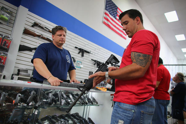 A gun store customer holds a National Armory AR-15 Battle Entry Assault Rifle in January 2013, as new gun control measures were being debated.