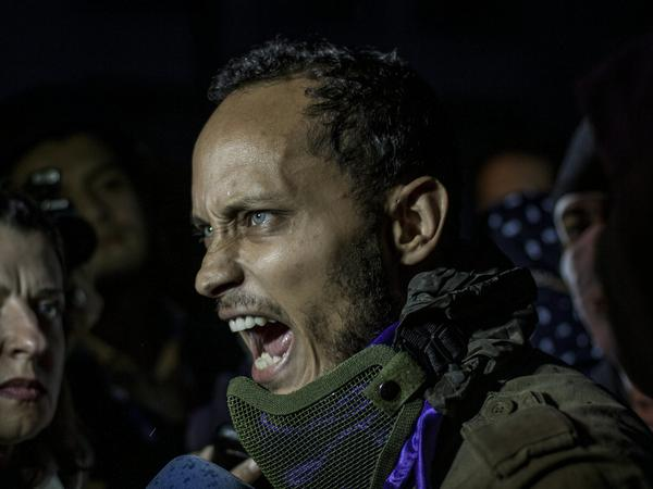 Oscar Perez speaks at an anti-government protest in Caracas on Thursday. Perez, a fugitive pilot who allegedly attacked the country's Supreme Court building with hand grenades thrown from a helicopter, appeared unexpectedly at an opposition rally before fleeing on a motorcycle.