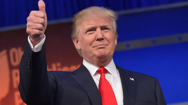 Donald Trump flashes the thumbs-up as he arrives on stage for the start of the prime time Republican presidential debate on August 6, 2015.