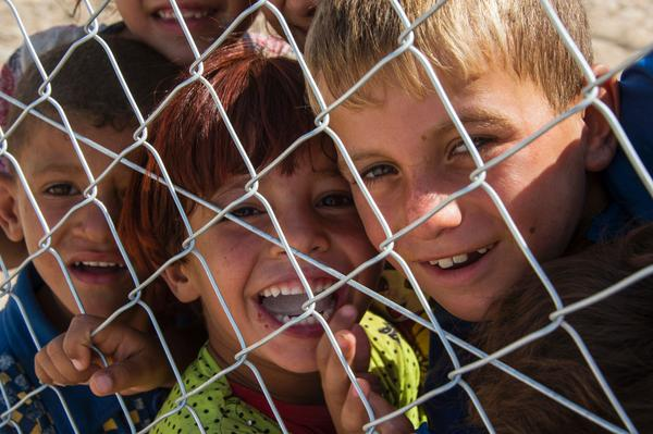 Chiildren smile and look through a fence at a UNHCR (United Nations High Commissioner for Refugees) refugee camp in Hammam al-Alil, on the outskirts of Mosul, on July 12, 2017.