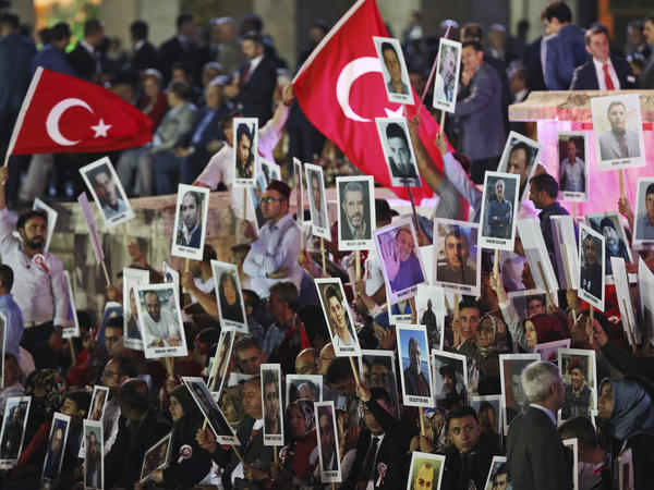 People hold photographs of the victims of the July 15, 2016 failed coup attempt, during a ceremony to commemorate the one year anniversary in Turkey's Parliament in Ankara, Turkey, early Sunday, July 16, 2017.